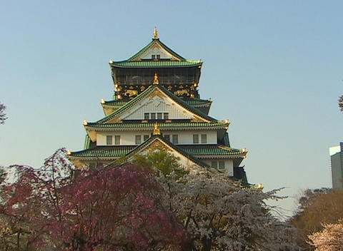 Worms-eye view of three-story green and gold Japanese temple surrounded by trees and other vegetatio Footage