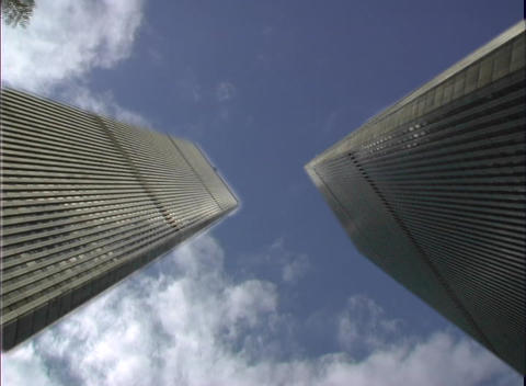 Skyscrapers rise to dizzying heights as clouds pass overhead in this low-angle shot Footage