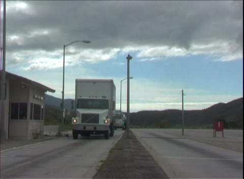 Semi trucks rush through a weigh station along the highway Stock Video Footage