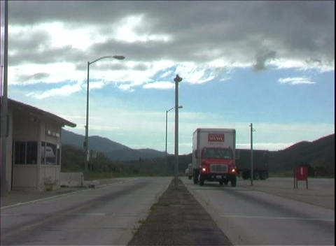 Semi trucks rush through a weigh station along the highway Footage