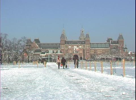 Pedestrians walk through the snow near a university Stock Video Footage