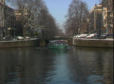 A water taxi travels through a canal in Amsterdam Stock Video Footage