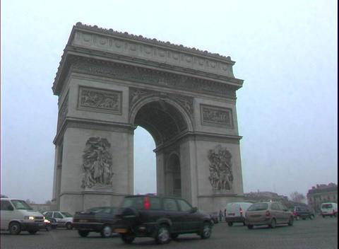 Traffic drives by the historic Arc de Triomphe in Paris, France with light snow falling Footage