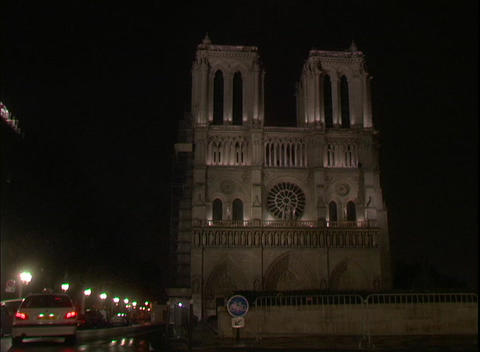 Lights illuminate the Notre Dame Cathedral at night in Paris, France Footage