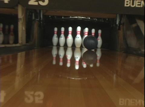 A blue bowling ball rolls down the lane knocking over nine pins Live Action