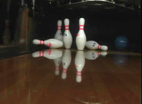A blue bowling ball rolls down the lane knocking over... Stock Video Footage