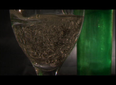 White wine and a lemon wedge fills a goblet Footage