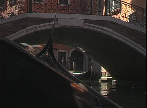 A water taxi cruises under a bridge and past gondolas... Stock Video Footage