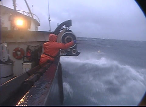 A lobster fishermen throws a rope out and catches a buoy in treacherous conditions while ocean fishi Footage