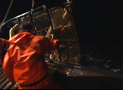 Crabbers pull a large crab-pot aboard their vessel Stock Video Footage