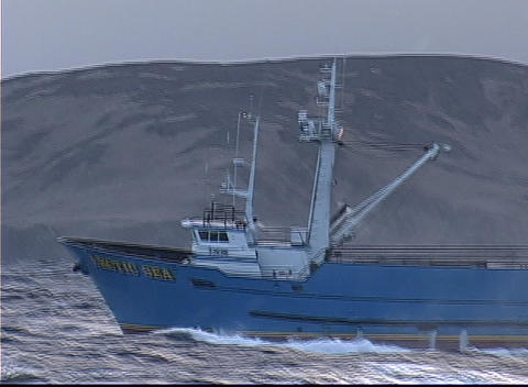 A crabber vessel breaks through the large waves of the Bearing Sea Live Action