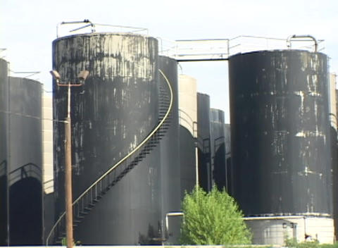 The camera pans across rows of large black industrial storage tanks Footage