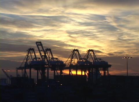 Medium shot of clouds flowing past shipping cranes in a large port Footage