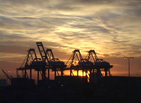 Medium shot of clouds flowing past shipping cranes in a... Stock Video Footage