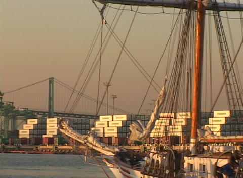 Medium shot of a sailing vessel passing through a cargo container port Footage