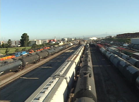 Pan-right across a railroad yard with freight trains and tanker cars Footage