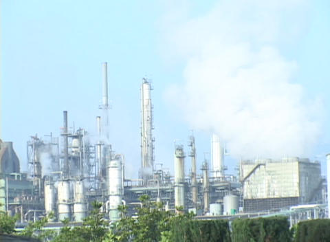 Time lapse of steam rising from a large oil refinery Stock Video Footage
