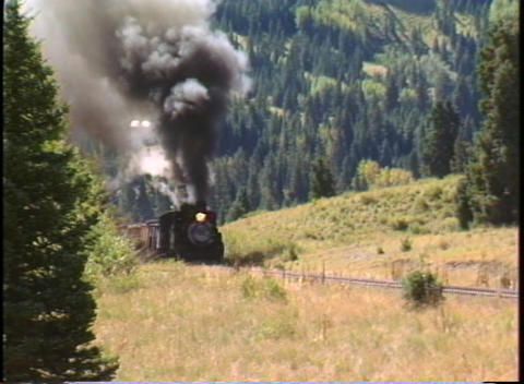 Pan-right shot of a steam freight train chug through the Colorado mountains Footage