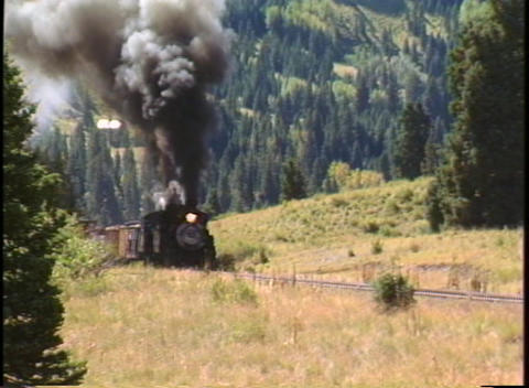 Pan-right shot of a steam freight train chug through the... Stock Video Footage