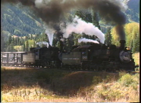 Tracking-right shot of two steam engines pulling a freight train through the Colorado Rockies Footage