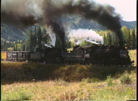Tracking-right shot of two steam engines pulling a... Stock Video Footage
