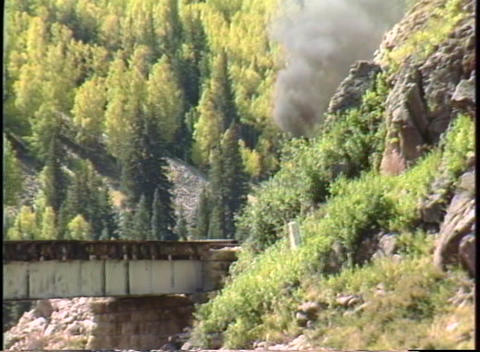 Following shot of a steam freight train crossing a bridge... Stock Video Footage