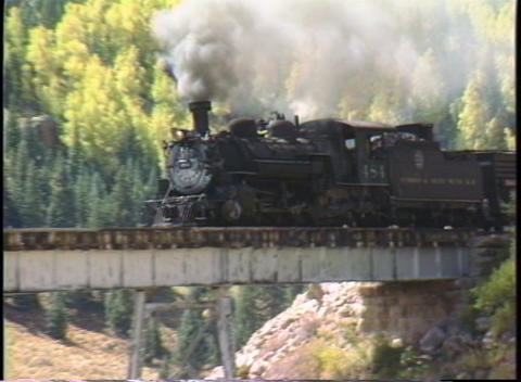 Following shot of a steam freight train crossing a bridge in the Colorado mountains Footage
