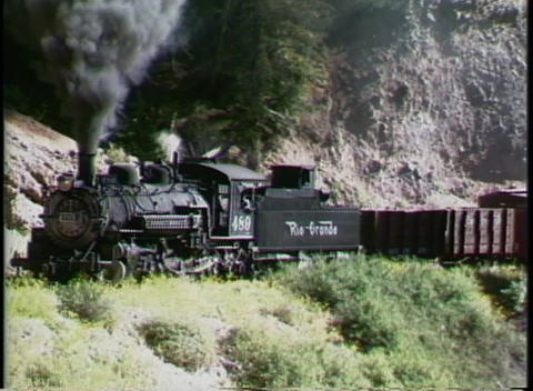 Following shot of a Rio Grande steam engine pulling a freight train through the Colorado mountains Footage