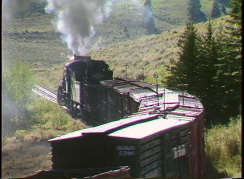Pan-left shot of a steam freight train entering a... Stock Video Footage