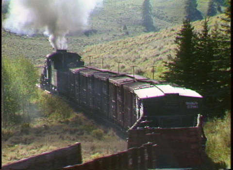 Pan-left shot of a steam freight train entering a mountain valley in Colorado Footage