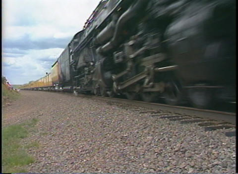 Tracking-out shot of a Union Pacific steam passenger train on a rural track in Colorado Footage