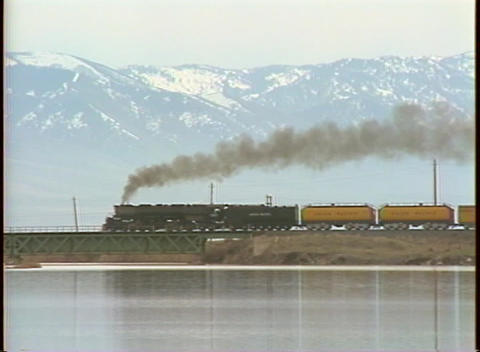 Tracking-right shot of a steam train passing in front of the Colorado Rocky Mountains Footage