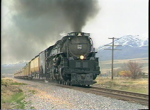 Tracking-out shot of a Union Pacific steam passenger train passing through a small Colorado town Footage