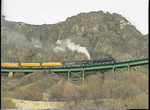 Following shot of a steam passenger train moving along a steep rocky cliff Footage