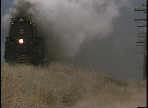 Tracking-out shot of steam billowing from a old-fashioned steam train Footage