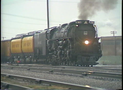 Tracking-right shot of a steam passenger train leaving a... Stock Video Footage