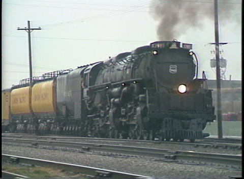 Tracking-right shot of a steam passenger train leaving a freight yard Footage