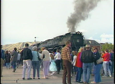 Medium shot of a crowd of rail buffs standing in front of a steam engine at a station Footage
