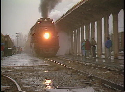 Pan-right shot of a steam passenger train pulling into a station on a rainy day Footage