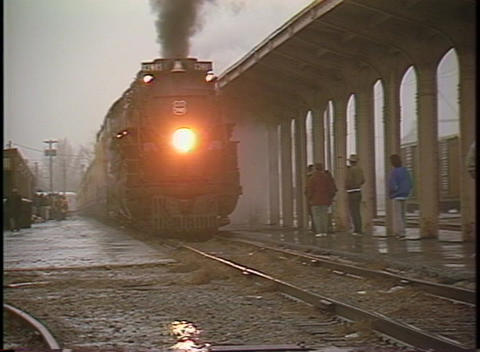 Pan-right shot of a steam passenger train pulling into a... Stock Video Footage