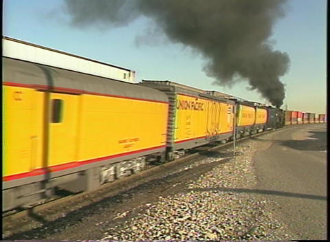 Medium shot of a Union Pacific train moving through a freight yard Footage