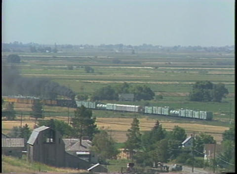 Long shot of a steam train passing through the countryside Stock Video Footage