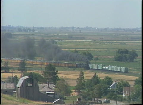 Long shot of a steam train passing through the countryside Footage