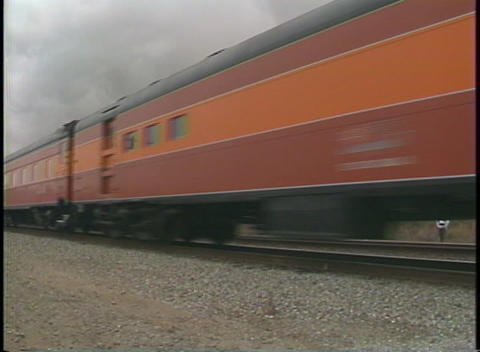 Pan-right shot of a vintage Southern Pacific passenger train passing by fast Footage
