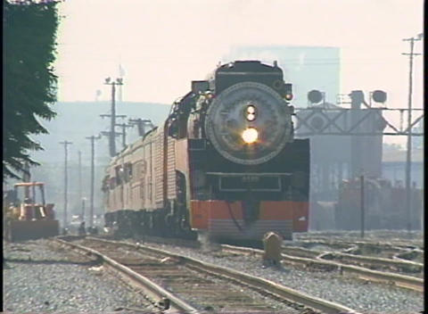 Zoom-out from a Southern Pacific steam passenger train approaching slowly Footage