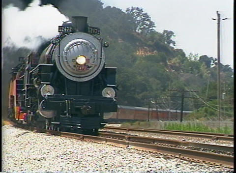 Tracking shot of a Southern Pacific steam passenger train rounding a bend in California Footage