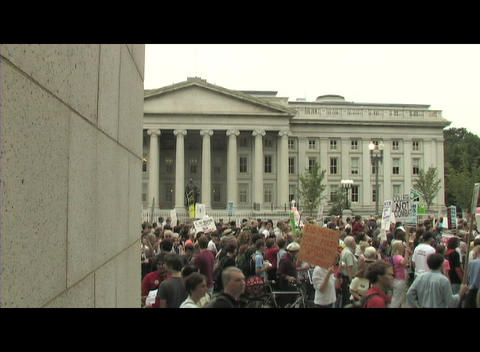 Long-shot of anti-war protesters marching past the . . Treasury building in Washington DC Footage