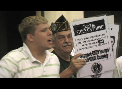 Medium-shot of a 20-something, Iraq-War supporter shouting in Washington DC Footage