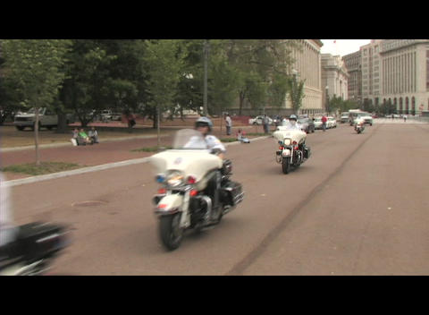 Following shot of motorcycle police-officers traveling down a Washington DC street Footage