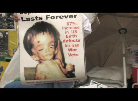Medium-shot of an anti-Iraq-War birth-defect sign Stock Video Footage